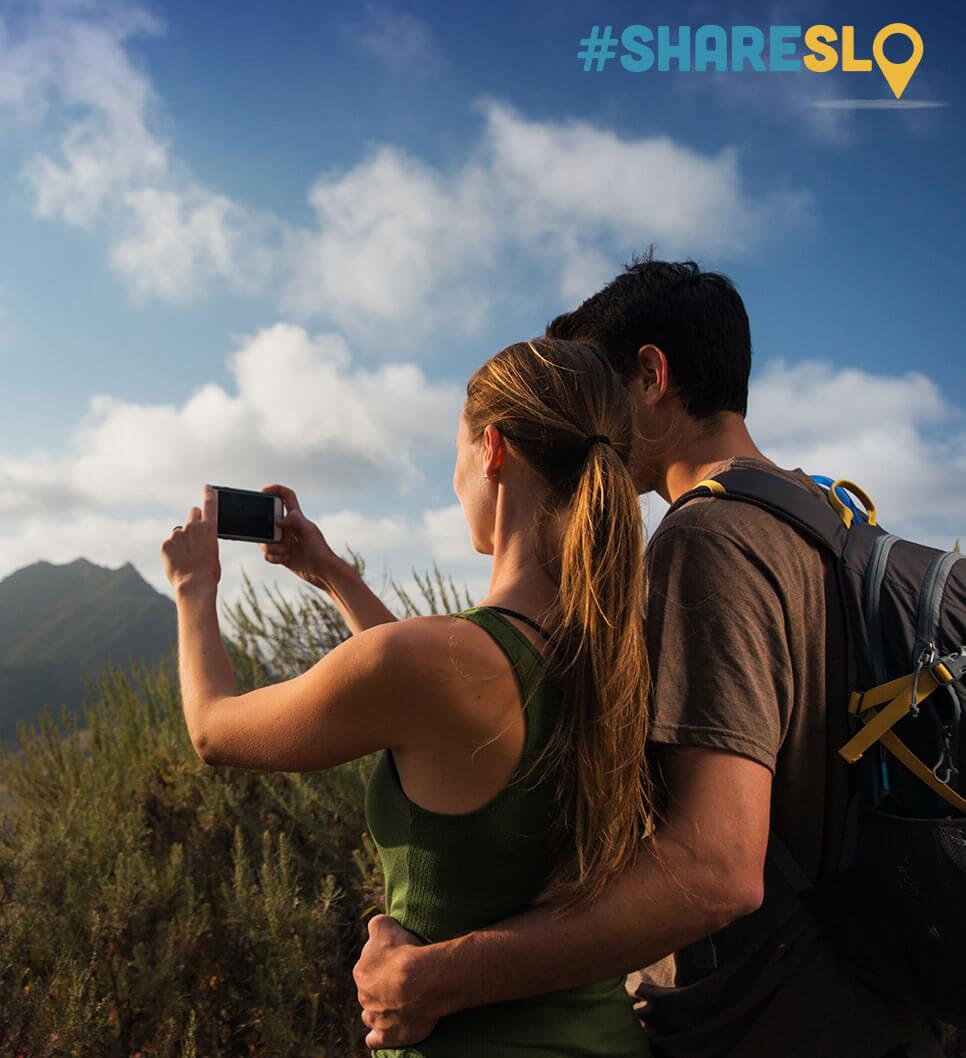 Couple taking photos of the views while hiking in San Luis Obispo
