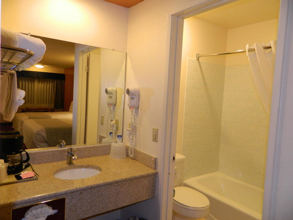 Shower, sink, and counter of a SLO INN room bathroom.