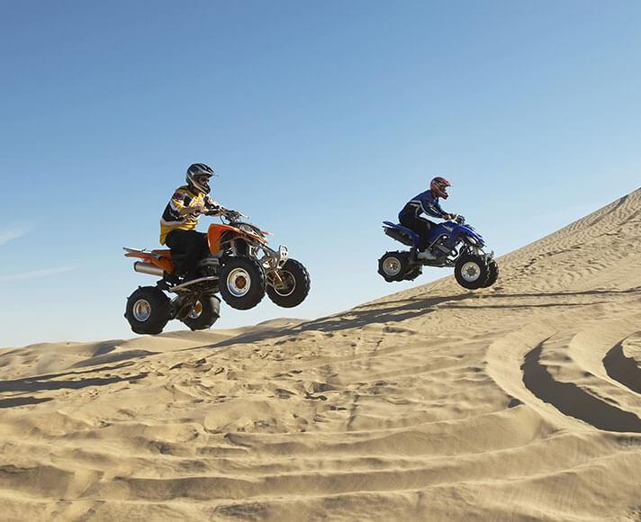 Two ATV riders soaring through the Oceano Dunes