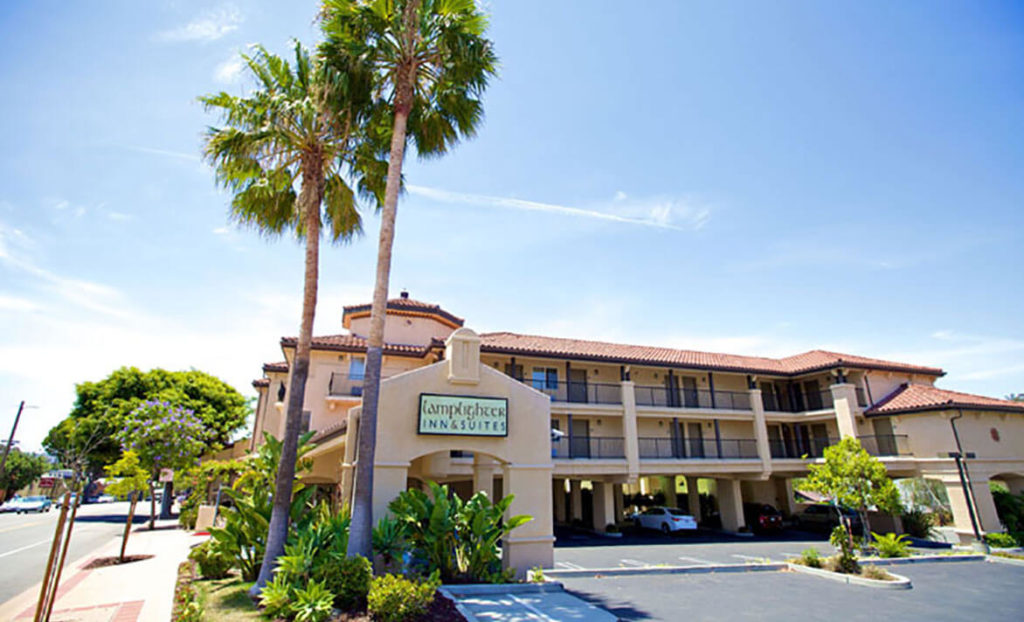 Welcome sign and outside view of Lamplight Inn & Suites San Luis Obispo