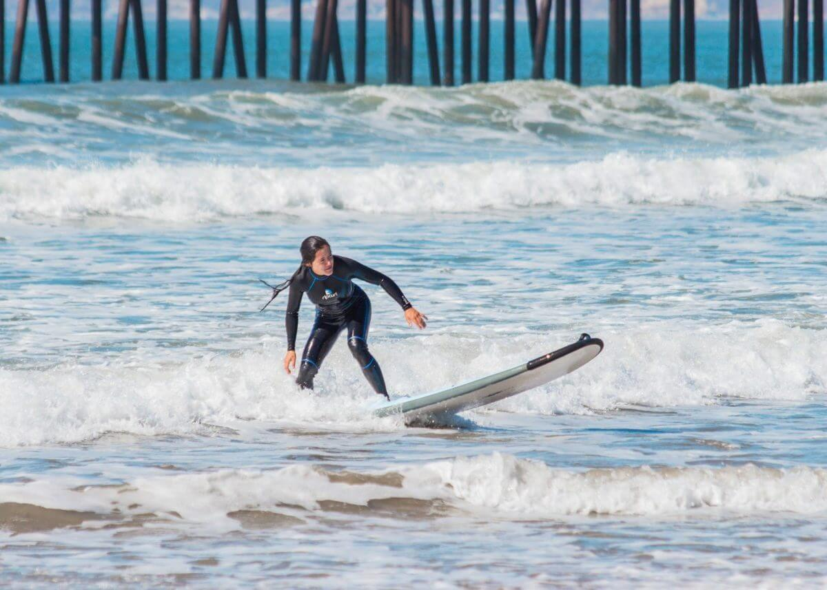 Adventure Aide Karlie Heynneman riding a wave by the pier