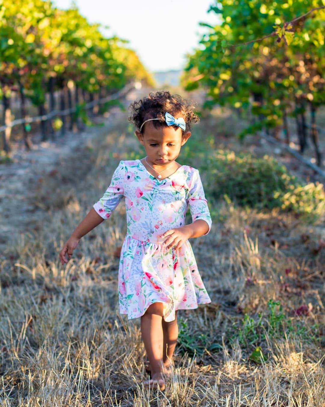 Little girl walking barefoot through the Tolosa Vineyards