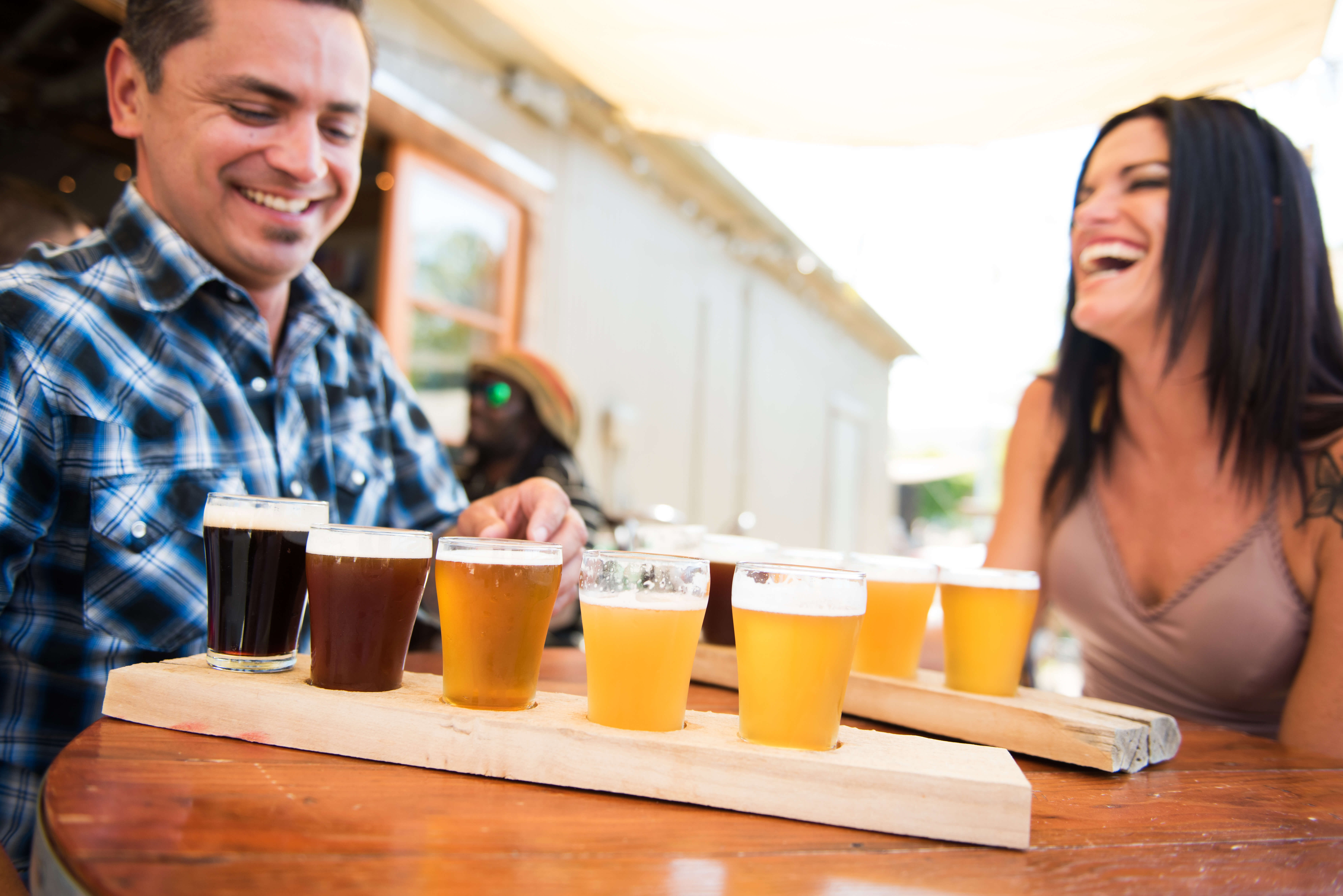 A man and woman enjoying their tours with beer flights from Bang the Drum Brewery in San Luis Obispo.