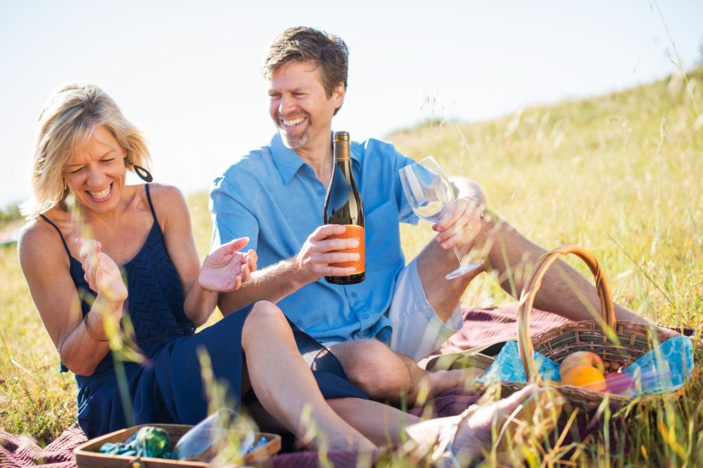 Photo of man and woman enjoying a bottle of wine on a grass field.