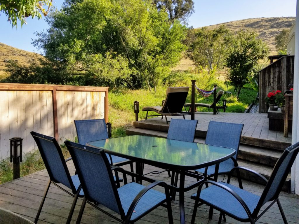 Bluerock Retreat Homestay Backyard patio with chairs around a dining table among the trees of San Luis Obispo.
