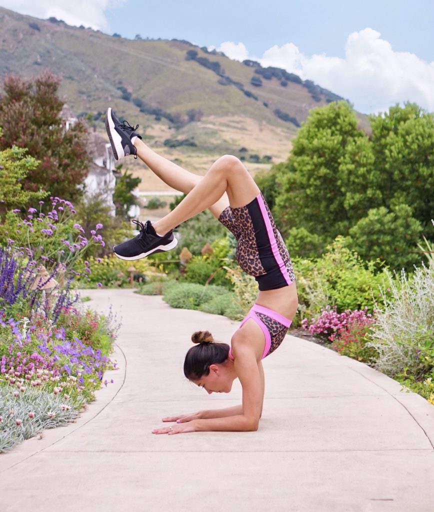 A woman hitting a yoga pose on the Cerro San Luis Trail in front of the mountain and flowers.