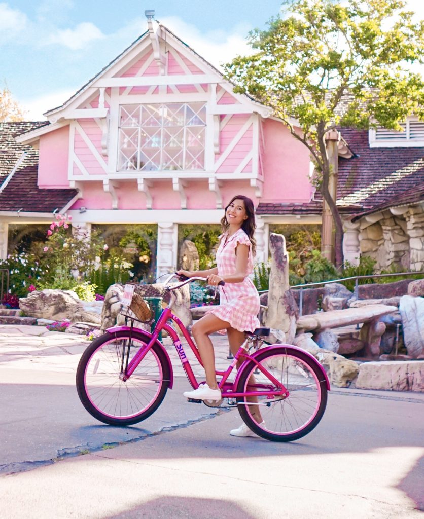 Wellness Influencer Mel Philips in front of Madonna Inn on a pink bike.