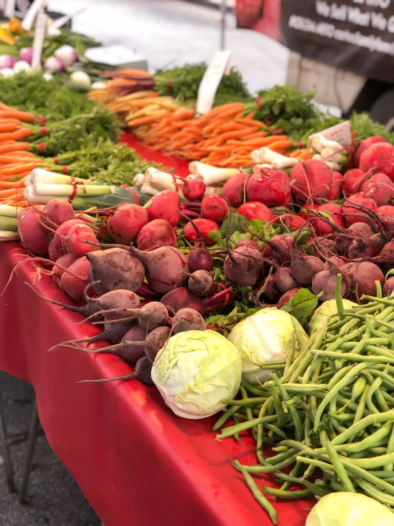 Cabbage, Beets, Turnips, Carrots, and Green Beans on a table at the Downtown SLO Farmer's Market