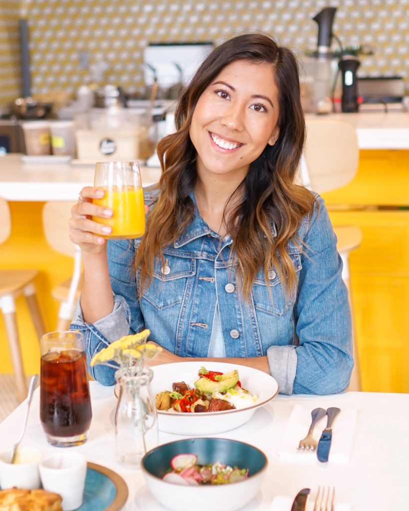 A young woman with dark hair at a table with breakfast and orange juice in hand at Farmhouse Corner Market in San Luis Obispo