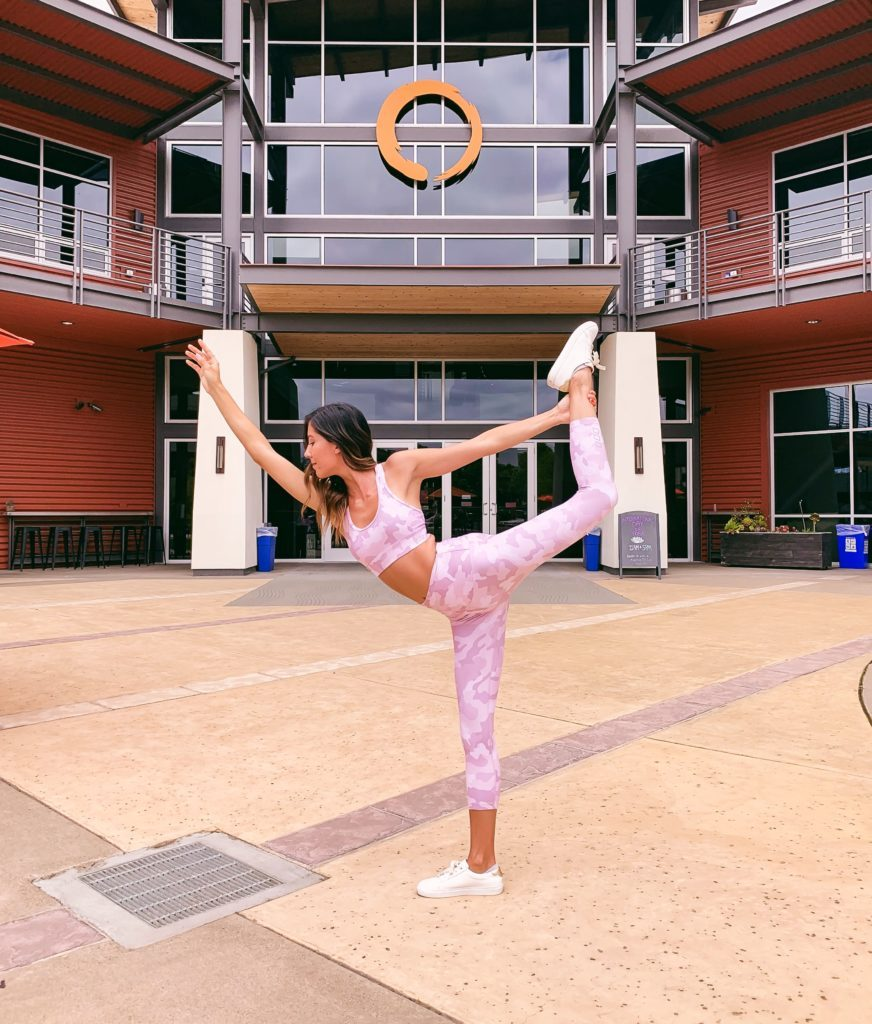 A woman in workout gear holding a yoga pose in front of Mindbody in San Luis Obispo