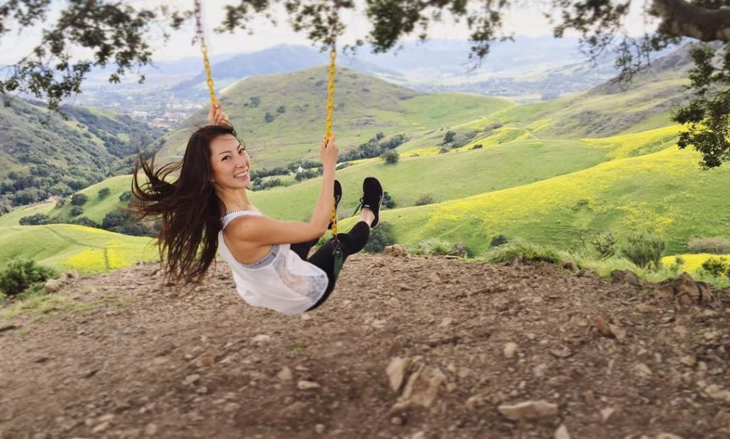 A smiling girl looking over her shoulder as she swings on the Serenity Swing in San Luis Obispo.