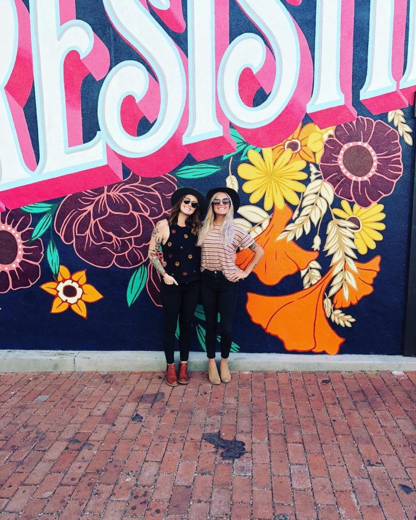 "2 smiling ladies in front of the San Luis Obispo mural reading, ""SLO Irresistible."" Photo by @sarah_tracy"