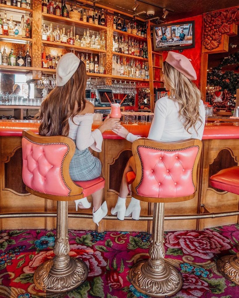 2 friends toasting pink milkshakes at the ornate, pink-accented bar of the Madonna Inn's Cafe. Photo by @trippingwithmybff