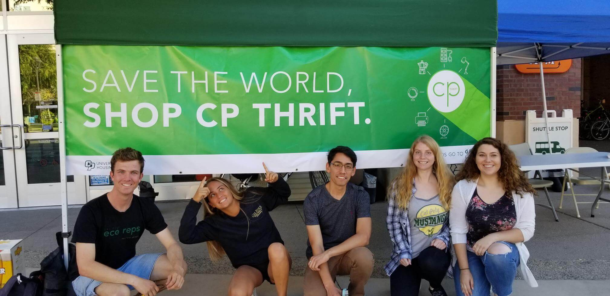 6 Cal Poly Students crouching in front of a CP Thrift green Banner.