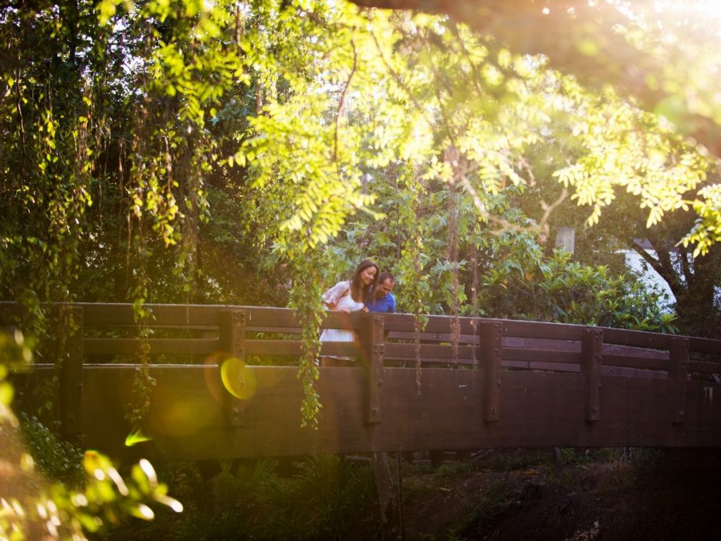 A couple looking over the shaded bridge at the San Luis Obispo Creek