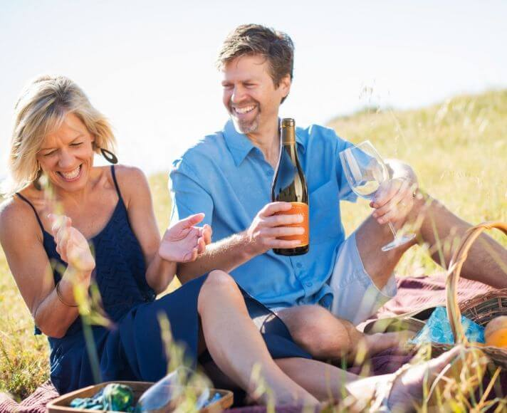 A smiling couple having a picnic with wine in the open San Luis Obispo hills.