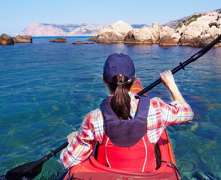 a girl kayaking in clear blue water
