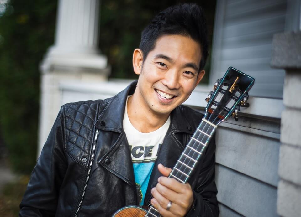 Guitarist, Jake Shimabukuro smiling with his guitar.