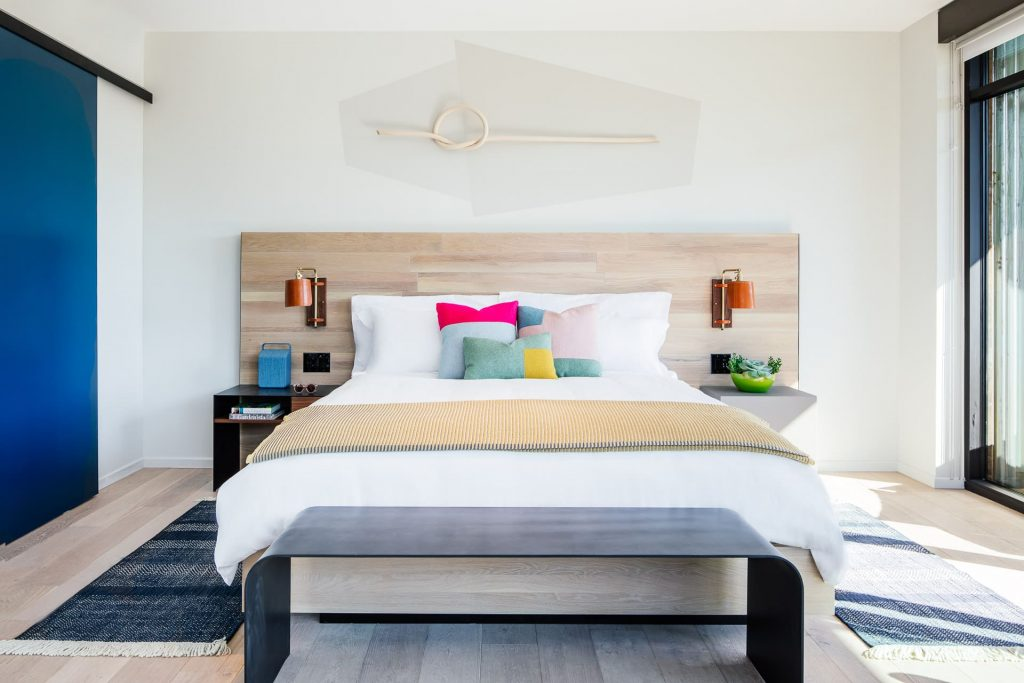 A clean, single bed with white sheets surrounded by modern fixtures in a Hotel San Luis Obispo room