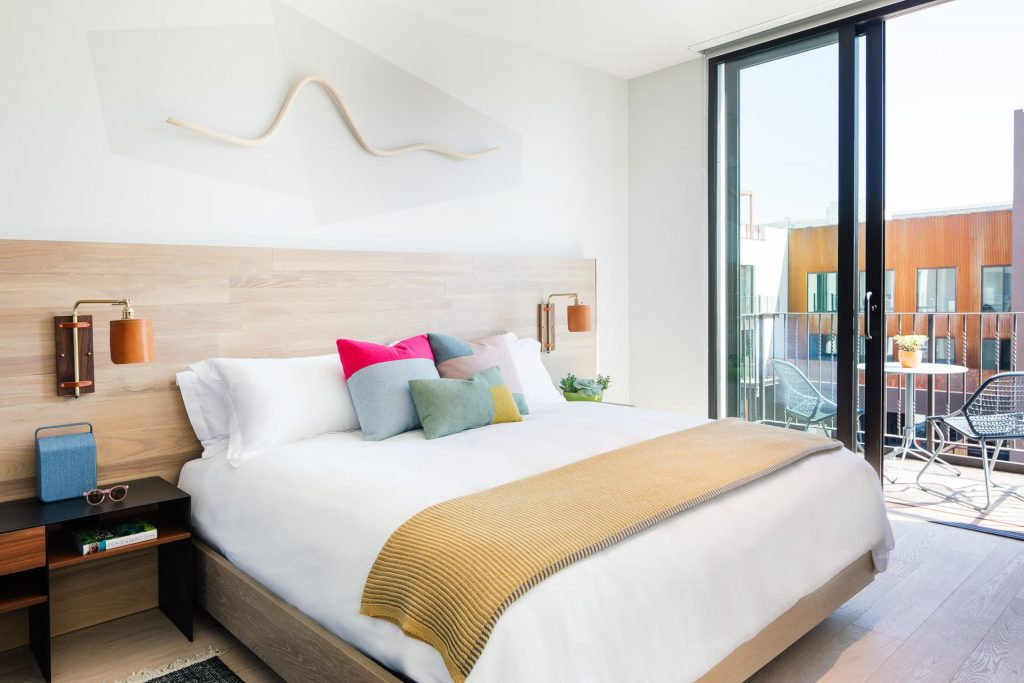 A clean bed with white sheets and colorful pillows, with a view out of a sliding glass door of the Hotel San Luis Obispo room's balcony.