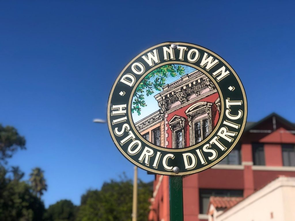 The round Downtown Historic District street sign in front of a brick building and blue sky in San Luis Obispo, California.