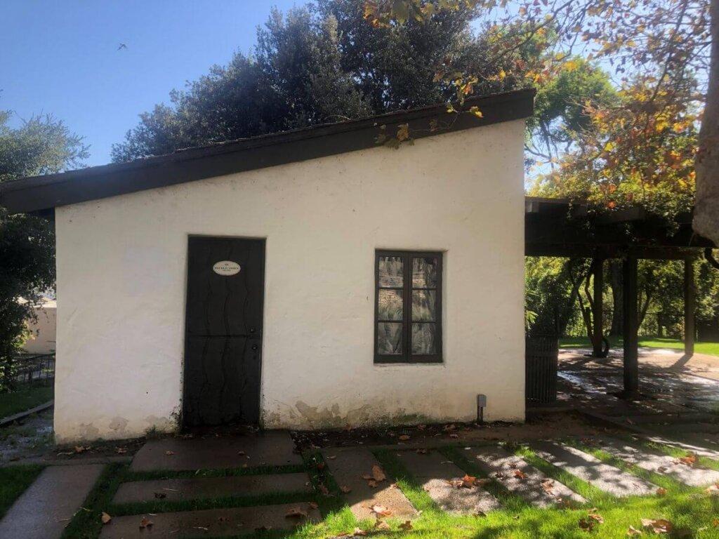 The front of the Murry Adobe, a small, white, historic home in San Luis Obispo, California.