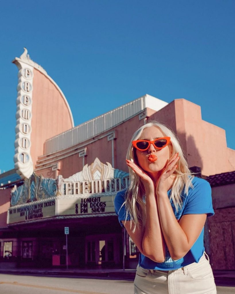 A young blond-haired woman with red, retro sunglasses blowing a kiss in front of the light-pink Fremont Theater in San Luis Obispo.