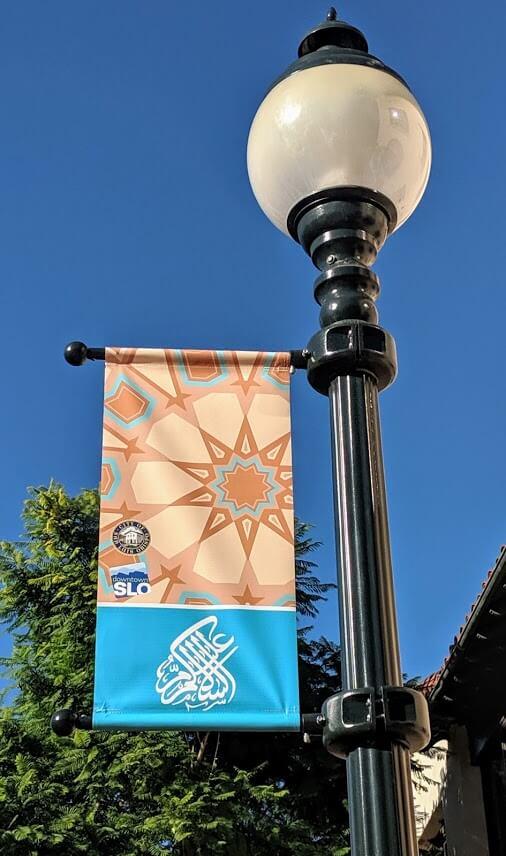 Downtown San Luis Obispo street light with a banner celebrating Assalamu Alaikum.