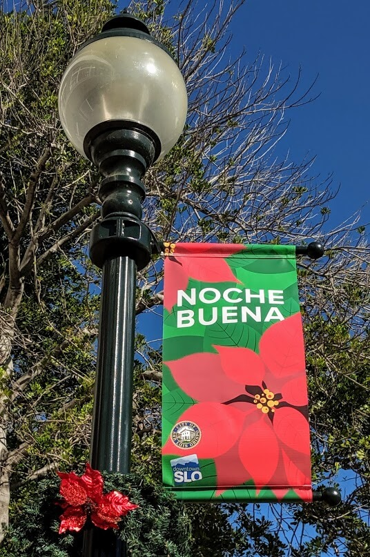 """A downtown San Luis Obispo street light with a banner that says, """"Noche Buena."""""""