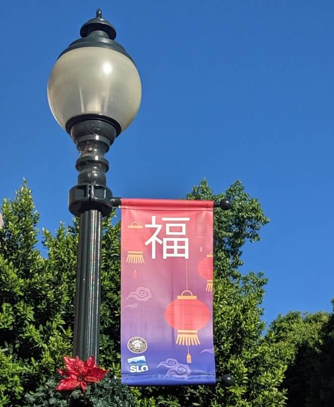 A downtown San Luis Obispo street light with a holiday banner celebrating Chinese New Years.