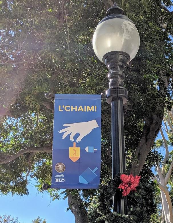 A downtown San Luis Obispo street light with a banner celebrating Hanukkah.