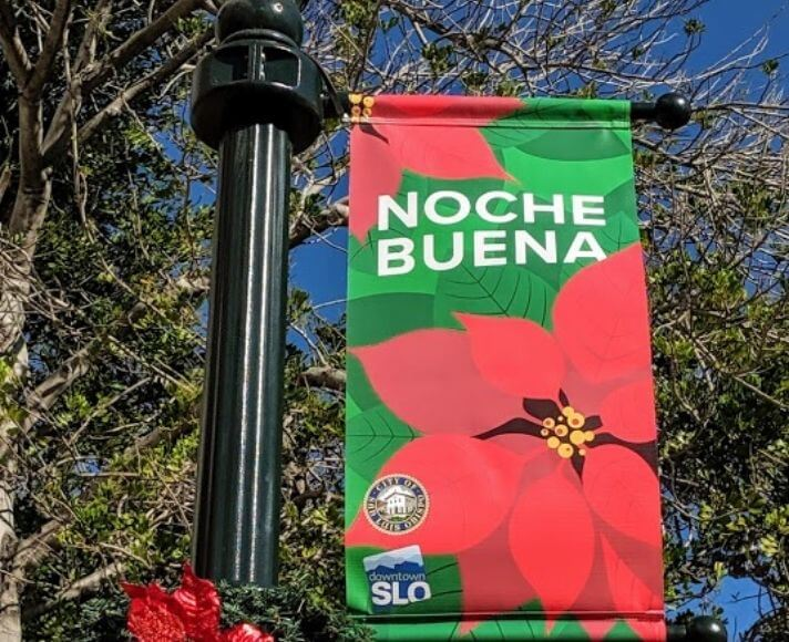 A downtown SLO street light with a Noche Buena banner.