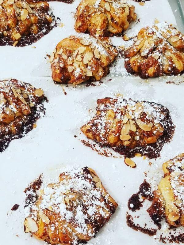 Flaky Pastries on parchment paper with a dusting of powdered sugar Joliene Bakery in San Luis Obispo.