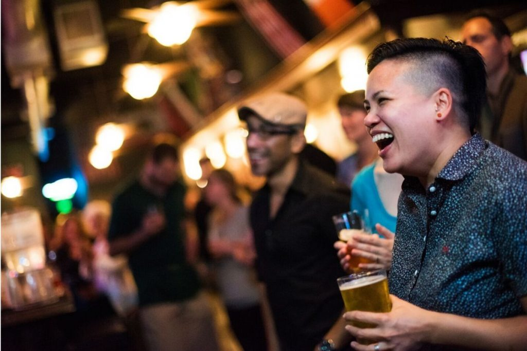Laughing people in a dim bar, holding pints of beer in hand.