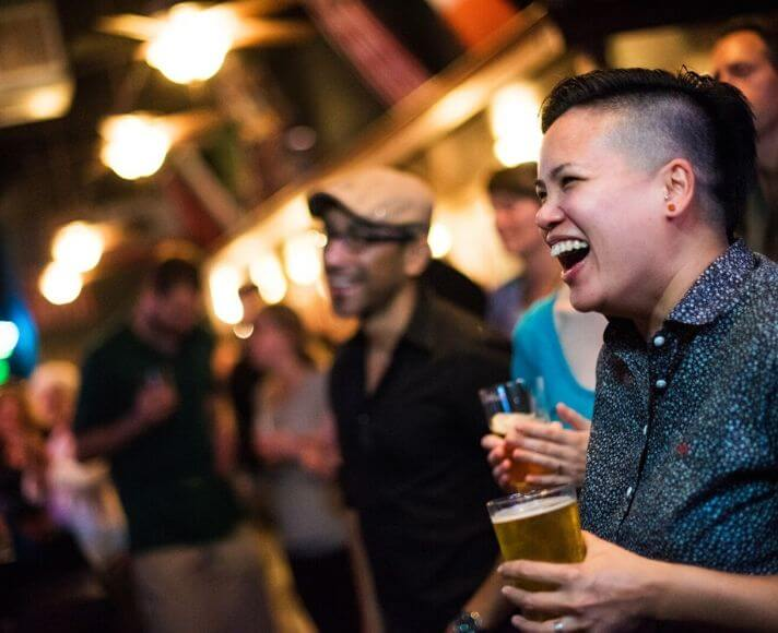 Young people enjoying live music in a bar while laughing with pints in hand.