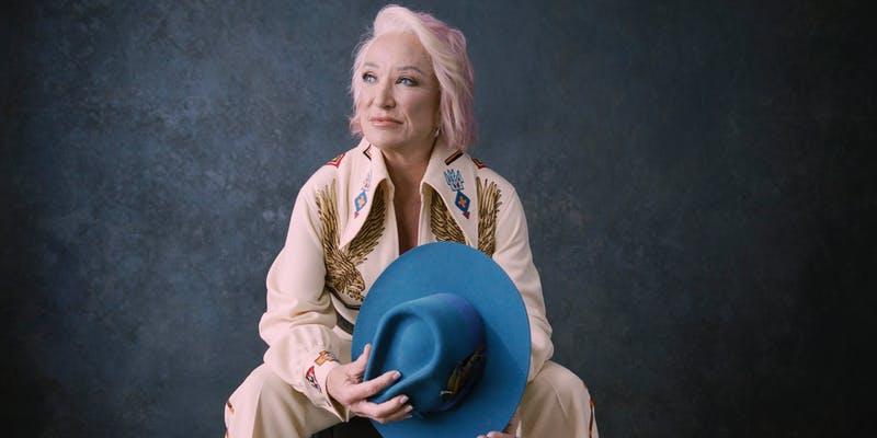 Tanya Tucker with a country-western suit and a blue cowboy hat in hand.