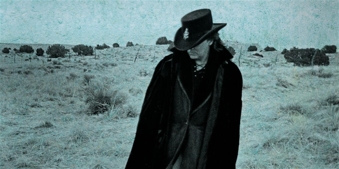 Marty Stuart in a trench coat and cowboy hat in a blurry desert.