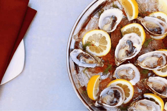 Oysters on ice with lemon wheels from above.