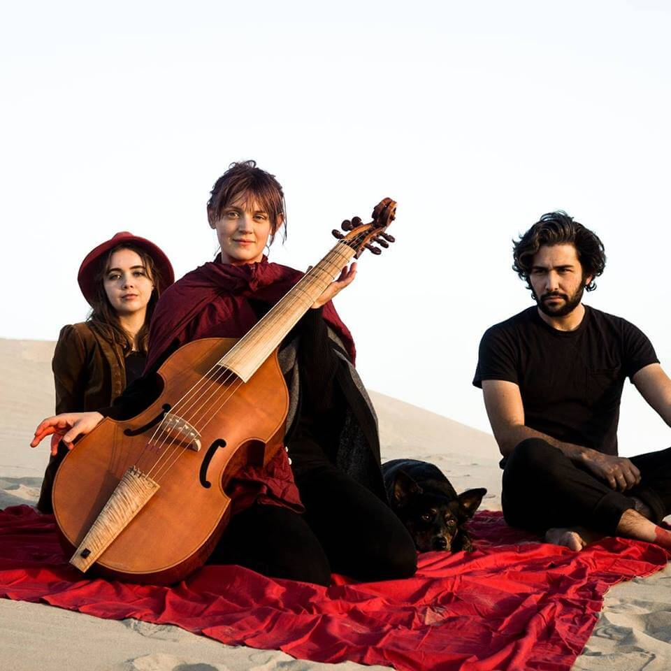 Arthur Watership and 2 other bandmates with a cello on a red blanket at the sand dunes.