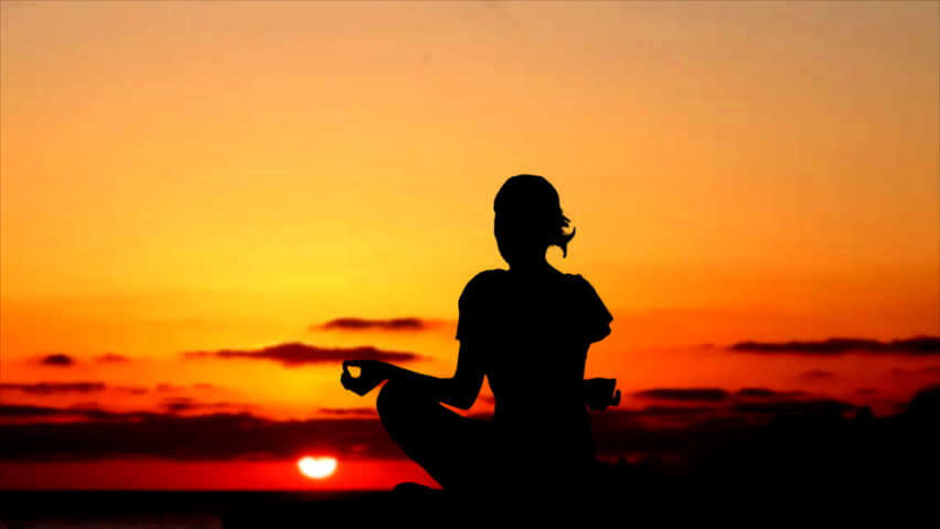 Meditation silhouette at sunset.