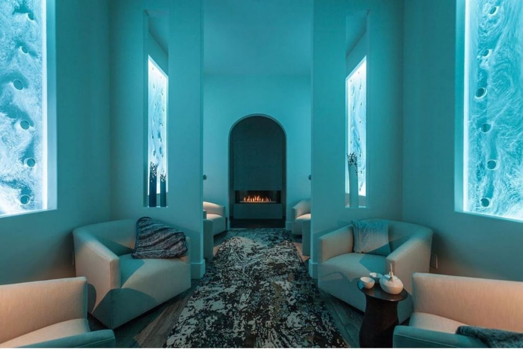 Hotel Cerro Spa's blue, high walls with couches along the sides of the hall.