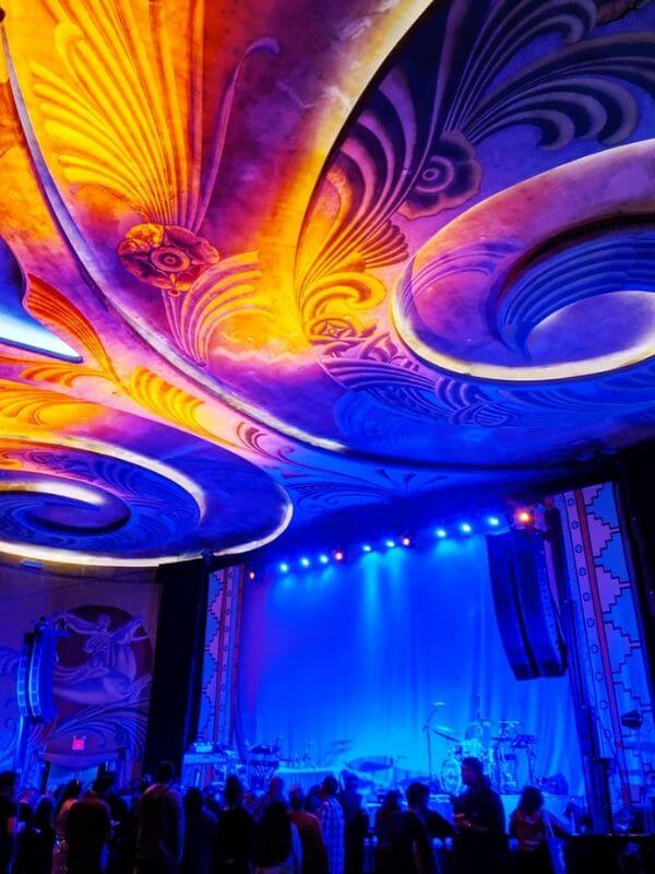Fremont Theater stage with blue lights and bright, swirling designs on the ceiling.