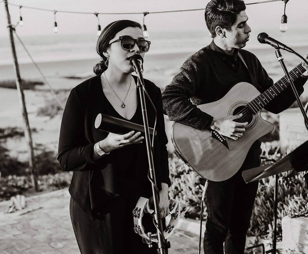 Elias and Madeline singing and playing guitar, dressed in black.