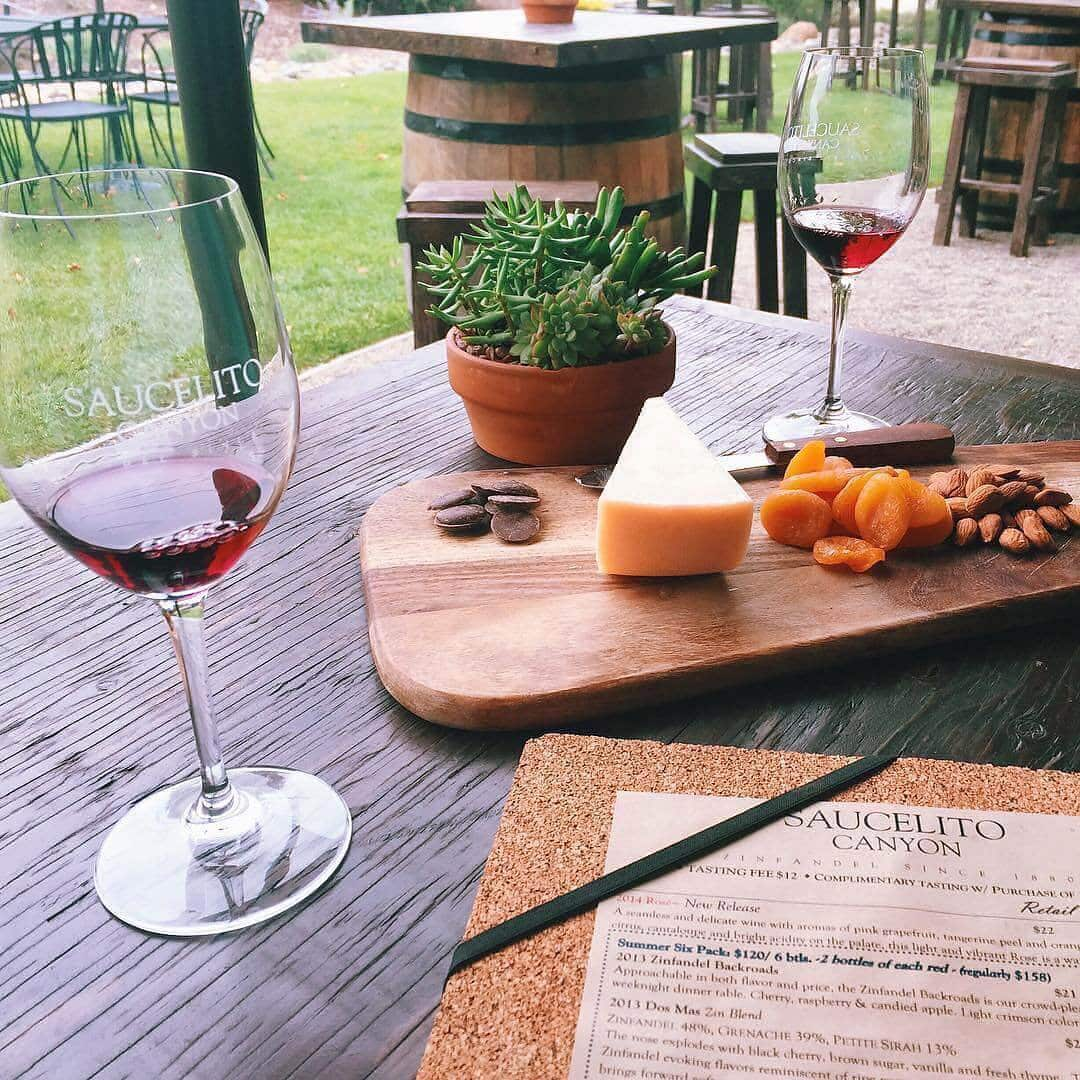 2 glasses of red wine with cheese and a menu at Saucelito Canyon Vineyard.